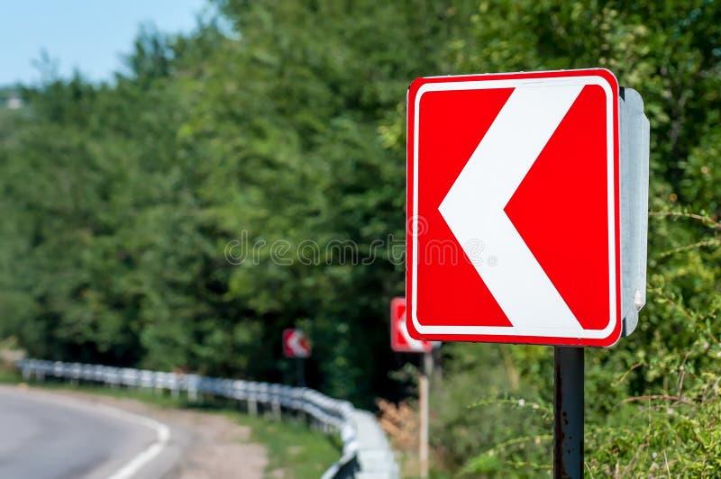 Signe du virage à gauche Les panneaux routiers avertissent d'un tour pointu laissé image stock
