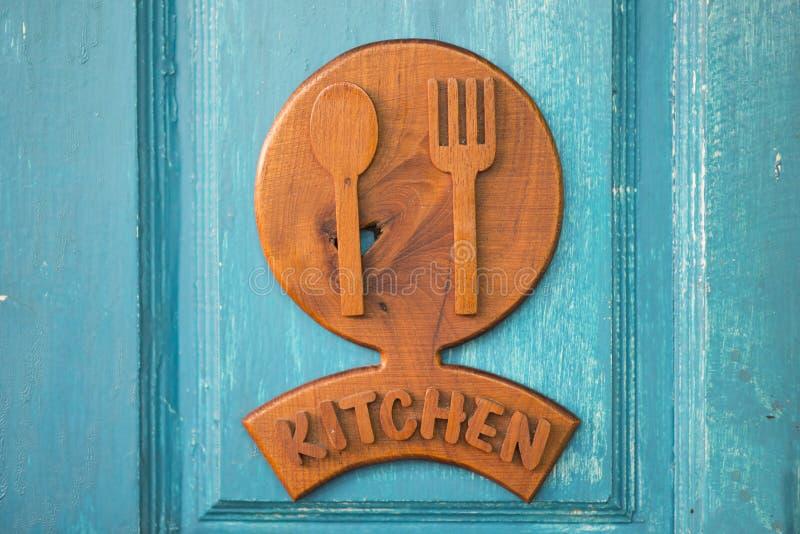 Signe en bois de cuisine accrochant sur la porte verte images libres de droits