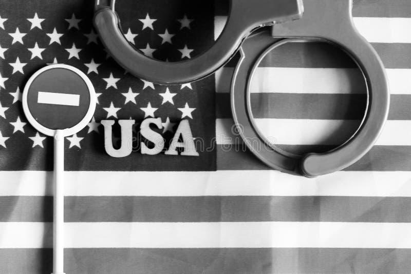 Signe et menottes d'arrêt de route sur un fond de drapeau de l'Amérique images stock