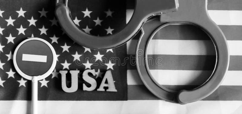 Signe et menottes d'arrêt de route sur un fond de drapeau de l'Amérique photographie stock libre de droits