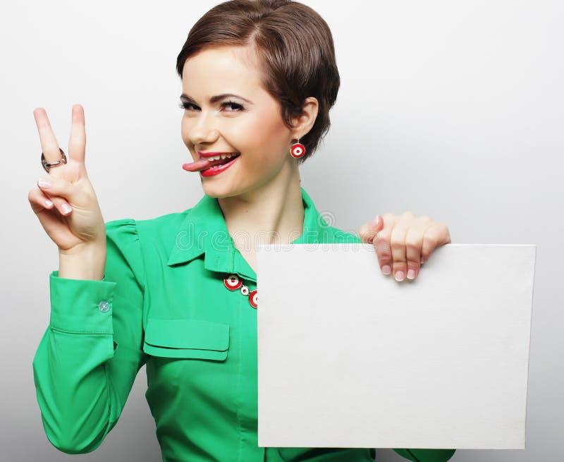 Signe heureux de blanc de participation de jeune femme occasionnelle photographie stock libre de droits