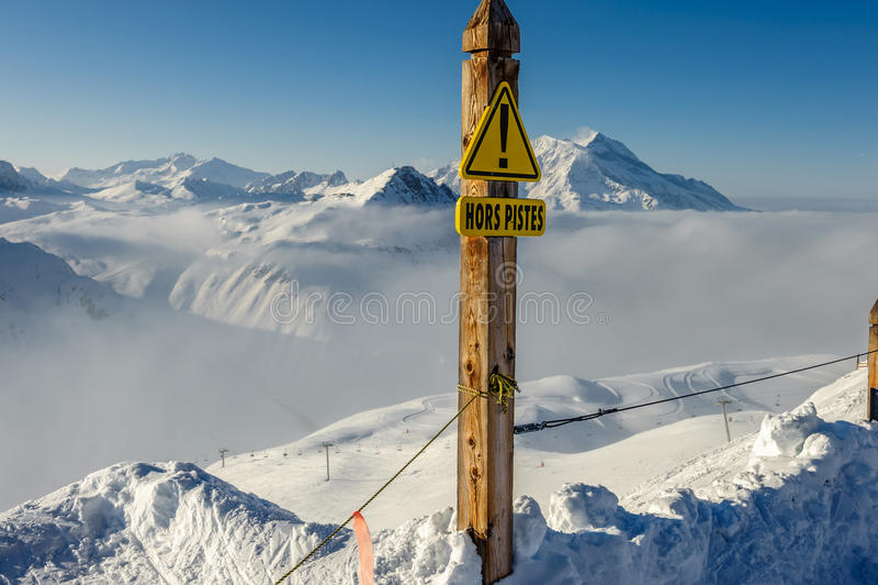 Signe hors-piste aux montagnes en nuages avec la neige en hiver photographie stock libre de droits