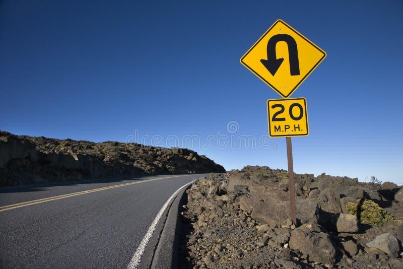 Signe le long d'une courbe sur une route. image stock