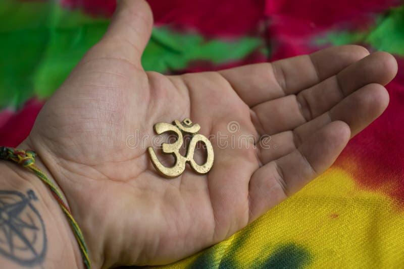 Signe OM de religion indoue et de Budhist sur la paume image stock