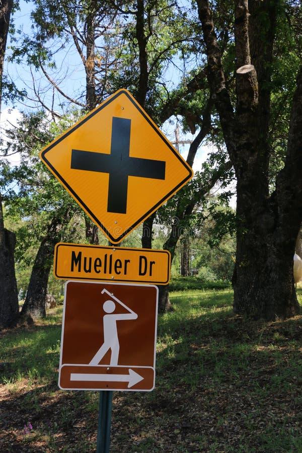 Signe orange et noir de croisement de route avec un signe de brun et blanc avec un homme balançant un club de golf photo libre de droits