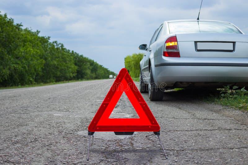 Signe rouge d'arrêt d'urgence et voiture argentée cassée sur la route photos libres de droits