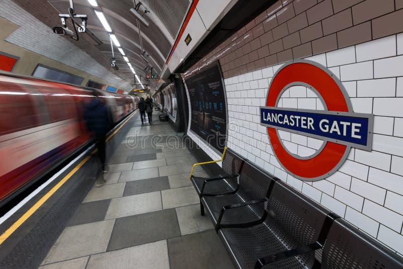 Signe souterrain de Londres avec le train et les personnes mobiles chez Lancaste images stock