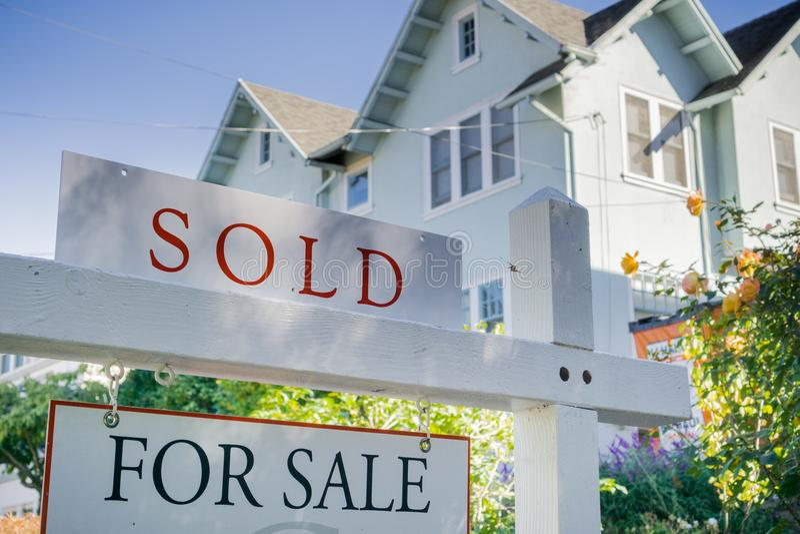Signe vendu devant une maison dans un voisinage résidentiel image stock
