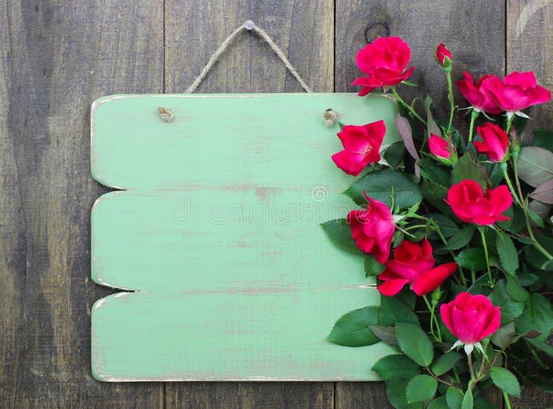 Signe vert vide affligé avec la frontière de fleur des roses rouges accrochant sur la porte en bois rustique image stock