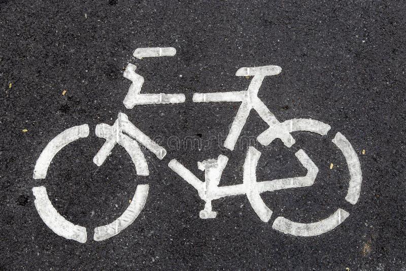 Signera cykel på väg med svart asfalt royaltyfria foton