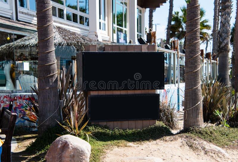 Signes vides noirs entre deux troncs de palmier sur une petite plage comme l'établissement devant un restaurant photo stock