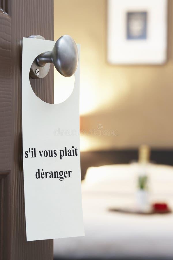 Signez avec le deranger vous de tresse de s'il français des textes (dérangez svp) accrochant sur la porte de chambre d'hôtel images libres de droits