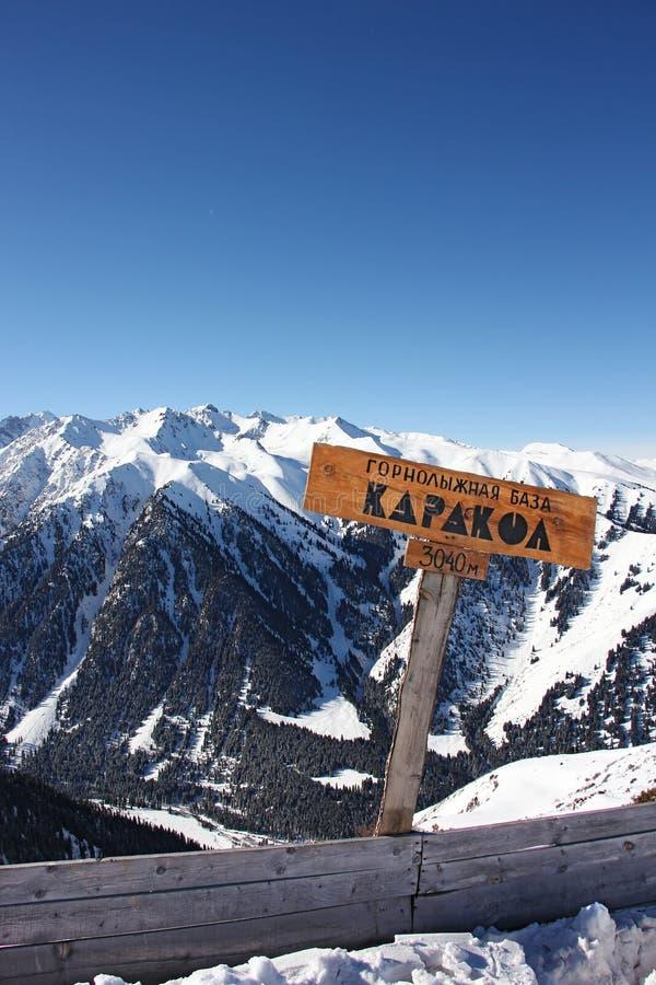 Signez avec le nom de la ville Karakol et la taille de la montagne photographie stock libre de droits