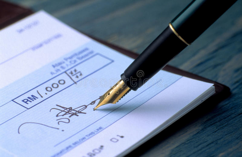 Signing cheque stock photo