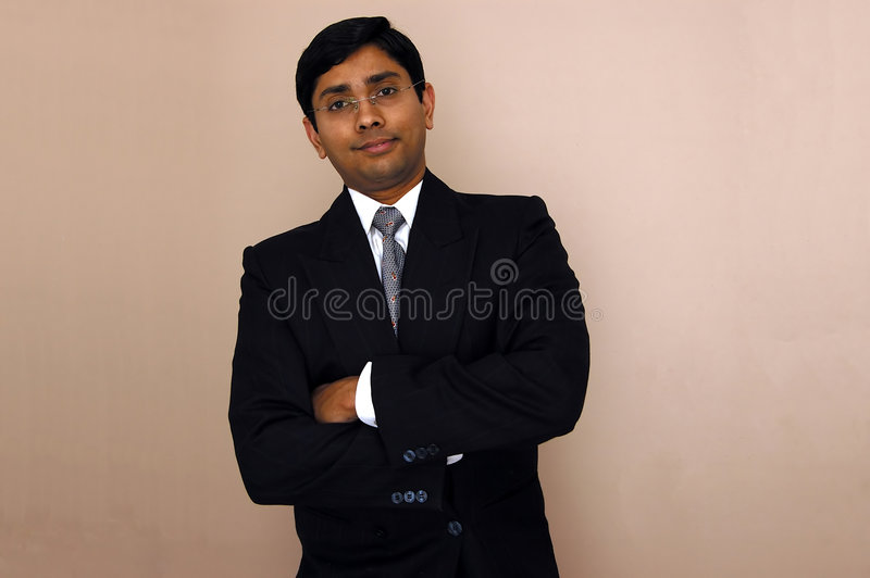 Signing a contract. Handsome Indian businessman signing a contract stock photo