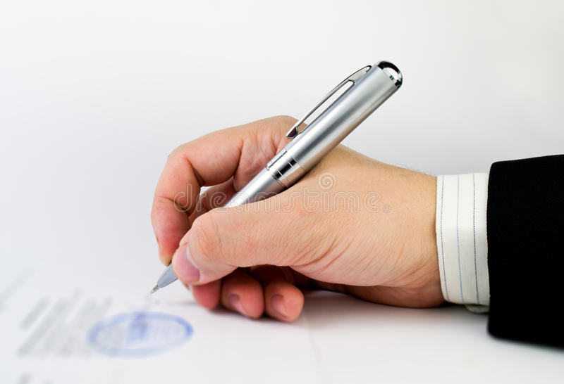 Signing a document. Hand with pen signing a document stock photography