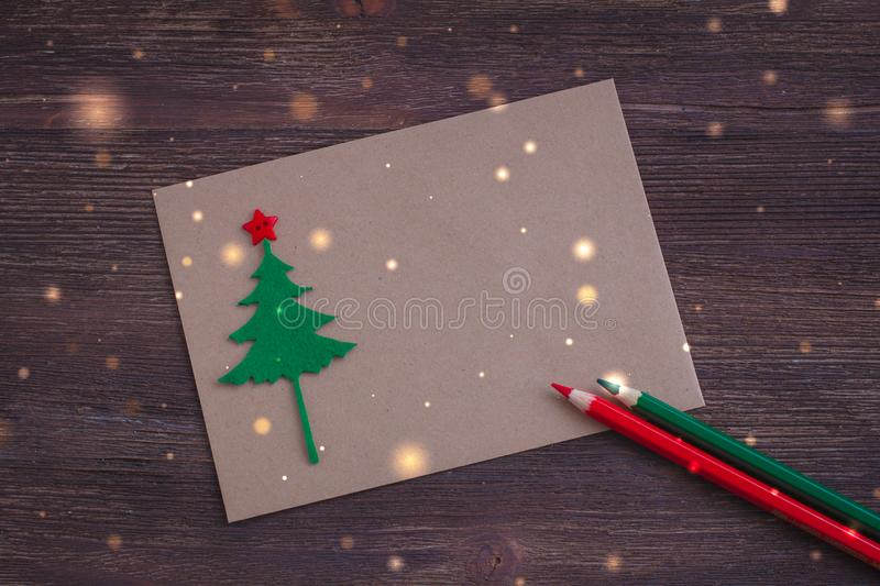 Signing handmade Christmas card with felt Christmas-tree, snowflakes effect and red star royalty free stock image