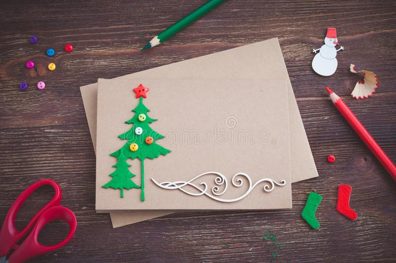 Signing handmade Christmas card with felt Christmas-tree, snowflakes effect and red star royalty free stock photos