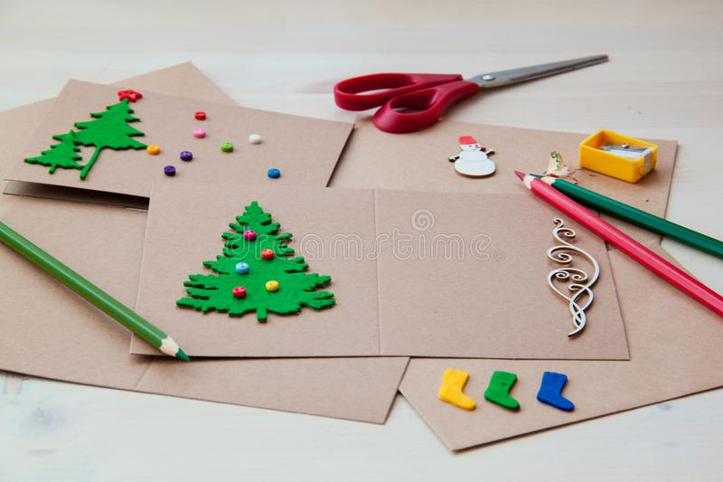 Signing Handmade Christmas cards. Felt, scissors, buttons, Christmas-tree, scrapping. Flat lay royalty free stock photos