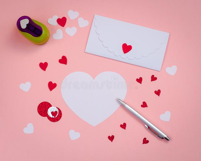 Signing Handmade Valentine cards. Felt, silver pen, white envelope. royalty free stock photos