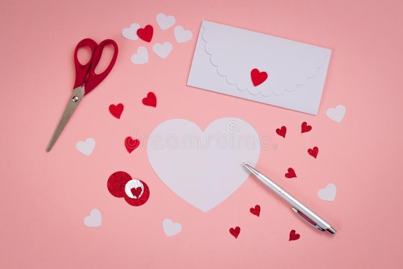 Signing Handmade Valentine`s cards. Felt, silver pen. white envelope, scissors. stock image