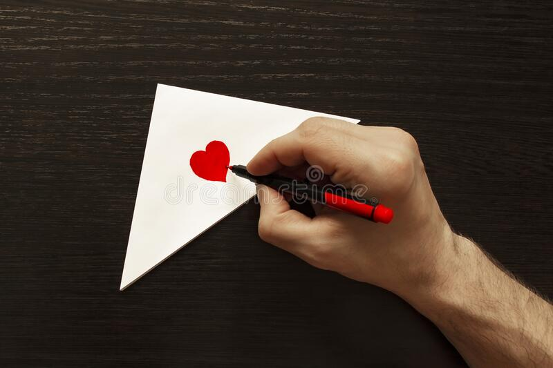 Romantic composition for Valentine`s day. Signing a love envelope with the inscription `I love you and my heart`. The photo shows one hand. Making a gift for an stock photography