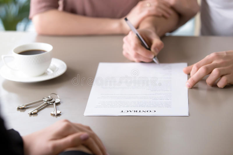 Signing mortgage contract. Family couple taking loan to buy prop stock photo