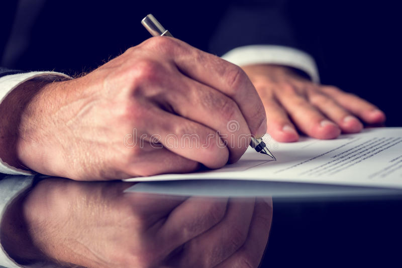 Signing mortgage papers. Closeup of male hand signing mortgage or other important legal or business document stock images
