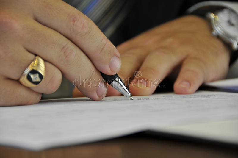Signing of official papers. Close up of hands of the person signing financial or official papers royalty free stock images