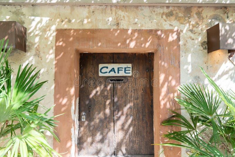 Signo de café retro grungy vintage en la pequeña puerta de madera del pueblo foto de archivo