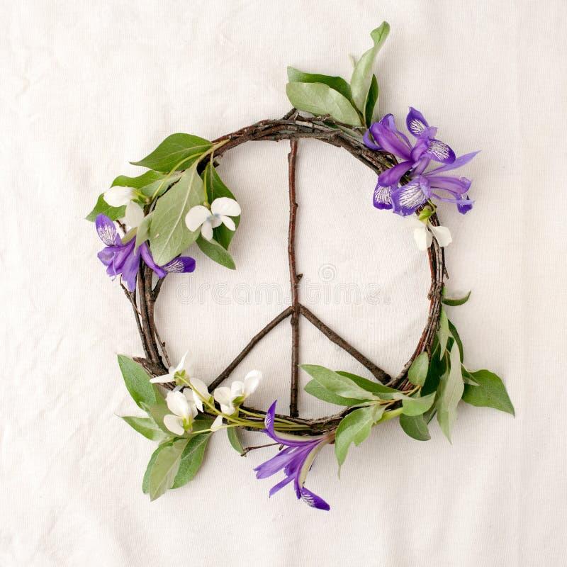 Signo de la paz, símbolo del material natural - flores, hojas, palillos de madera en fondo del blanco del tejido fotos de archivo libres de regalías