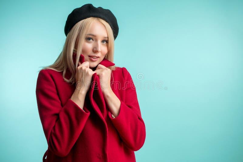 Signora abbastanza bionda sta scuotendo in rosso il cappotto fotografia stock