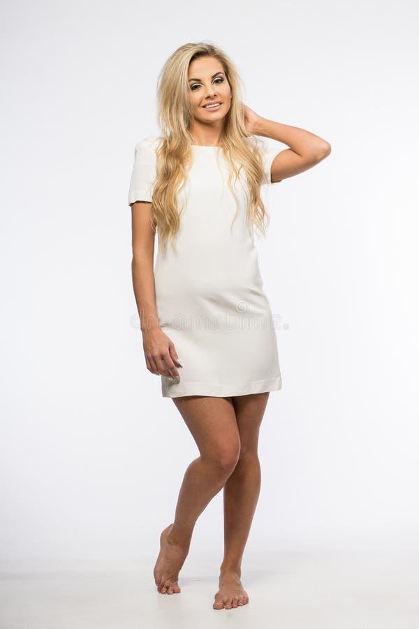 Signora in abito bianco che posa nello studio Bella donna elegante, capelli biondi lunghi in vestito da sera Ritratto di bellezza immagine stock