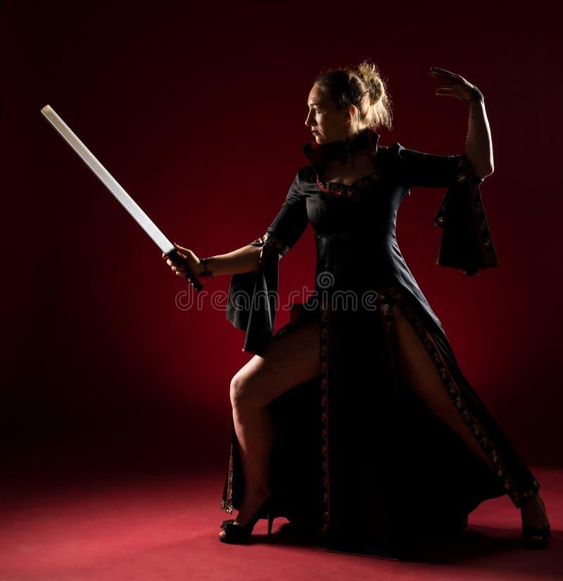 Signora in abito nero con una condizione della spada e posare nello studio Ritratto di bella donna elegante in vestito da sera fotografie stock libere da diritti