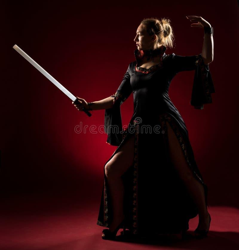 Signora in abito nero con una condizione della spada e posare nello studio Ritratto di bella donna elegante in vestito da sera immagini stock