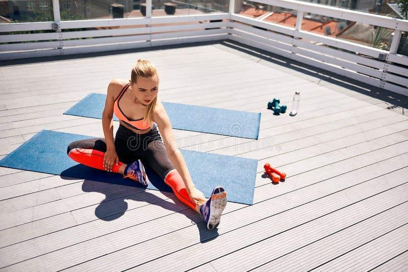 Signora adatta sta allungando le gambe sull'ampio balcone fotografie stock
