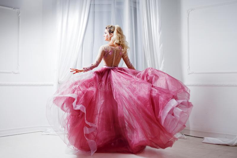Signora affascinante in un vestito rosa elegante con un treno Ritratto dello studio nell'interno bianco, vista posteriore immagini stock