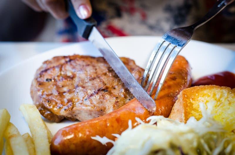 Signora affetta la bistecca della carne di maiale e della salsiccia sul piatto bianco fotografia stock