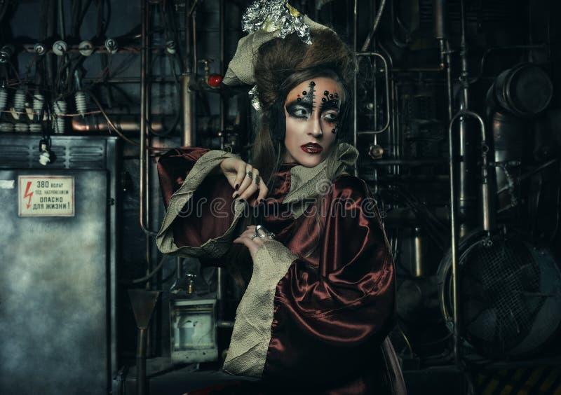 Signora alla moda aggressiva dello steampunk in un interno creativo Arte un concetto di modo fotografia stock