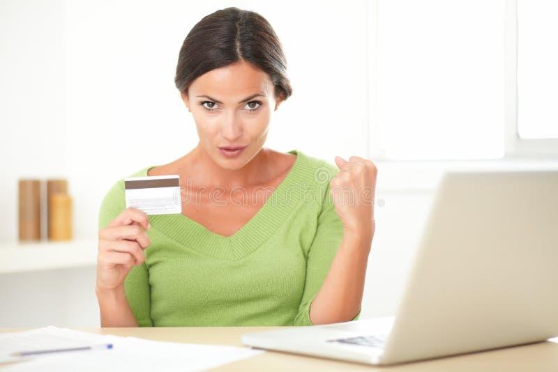 Signora allegra che per mezzo del suo computer portatile per l'acquisto online fotografia stock