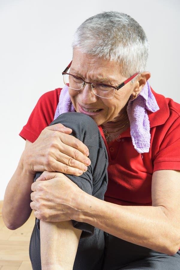 Signora anziana che avverte dolore del ginocchio immagini stock