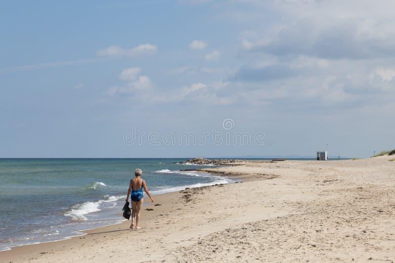 Signora anziana che cammina sulla spiaggia in Danimarca fotografia stock