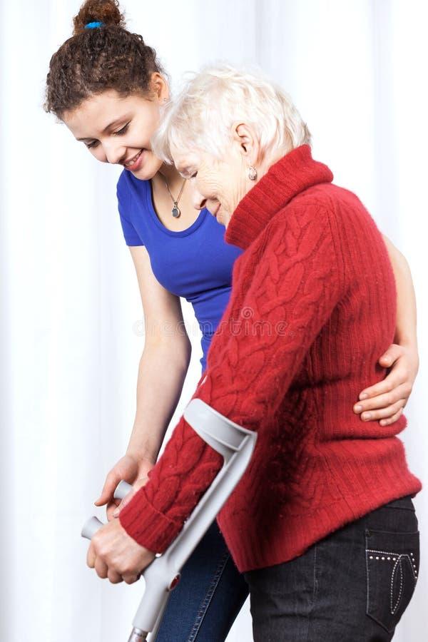 Signora anziana che cammina sulle grucce fotografia stock
