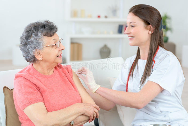 Signora anziana che ottiene iniezione a casa immagini stock libere da diritti