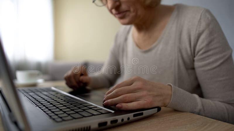 Signora anziana che prova a scrivere sul computer portatile a casa, corsi di computer, addestramento online fotografia stock