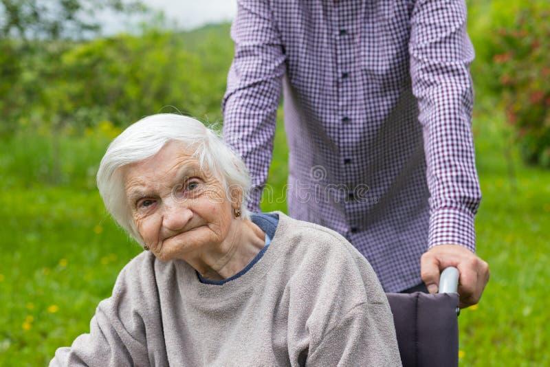 Signora anziana con demenza in una sedia a rotelle ed in un personale sanitario immagini stock libere da diritti