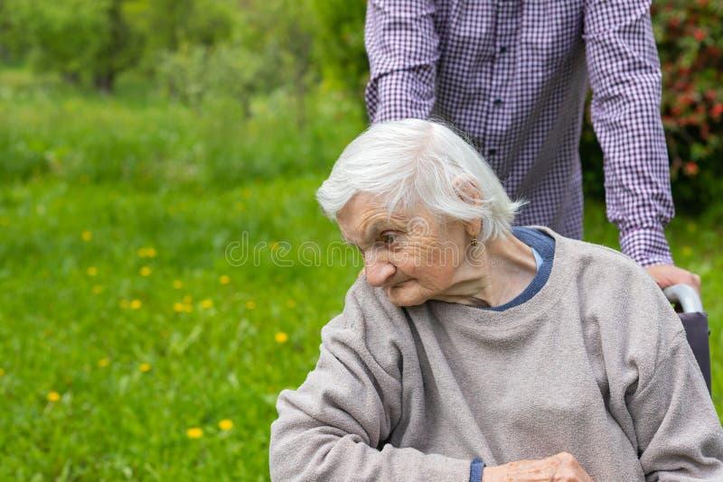 Signora anziana con demenza in una sedia a rotelle ed in un personale sanitario immagini stock