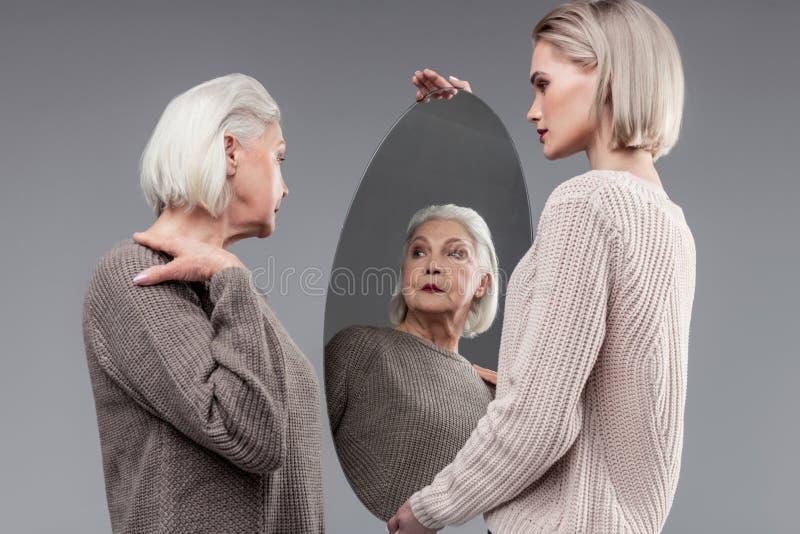 Signora anziana dai capelli corti che posa mentre controllandosi su in specchio fotografie stock