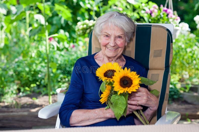 Signora anziana felice Sitting sui girasoli della tenuta della sedia fotografia stock libera da diritti