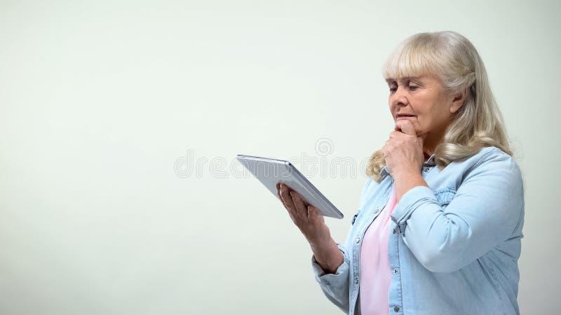 Signora anziana premurosa facendo uso della compressa, app contare online, tecnologie moderne immagine stock